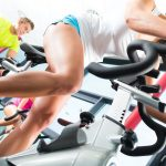 Young People - women and men - exercising in the gym