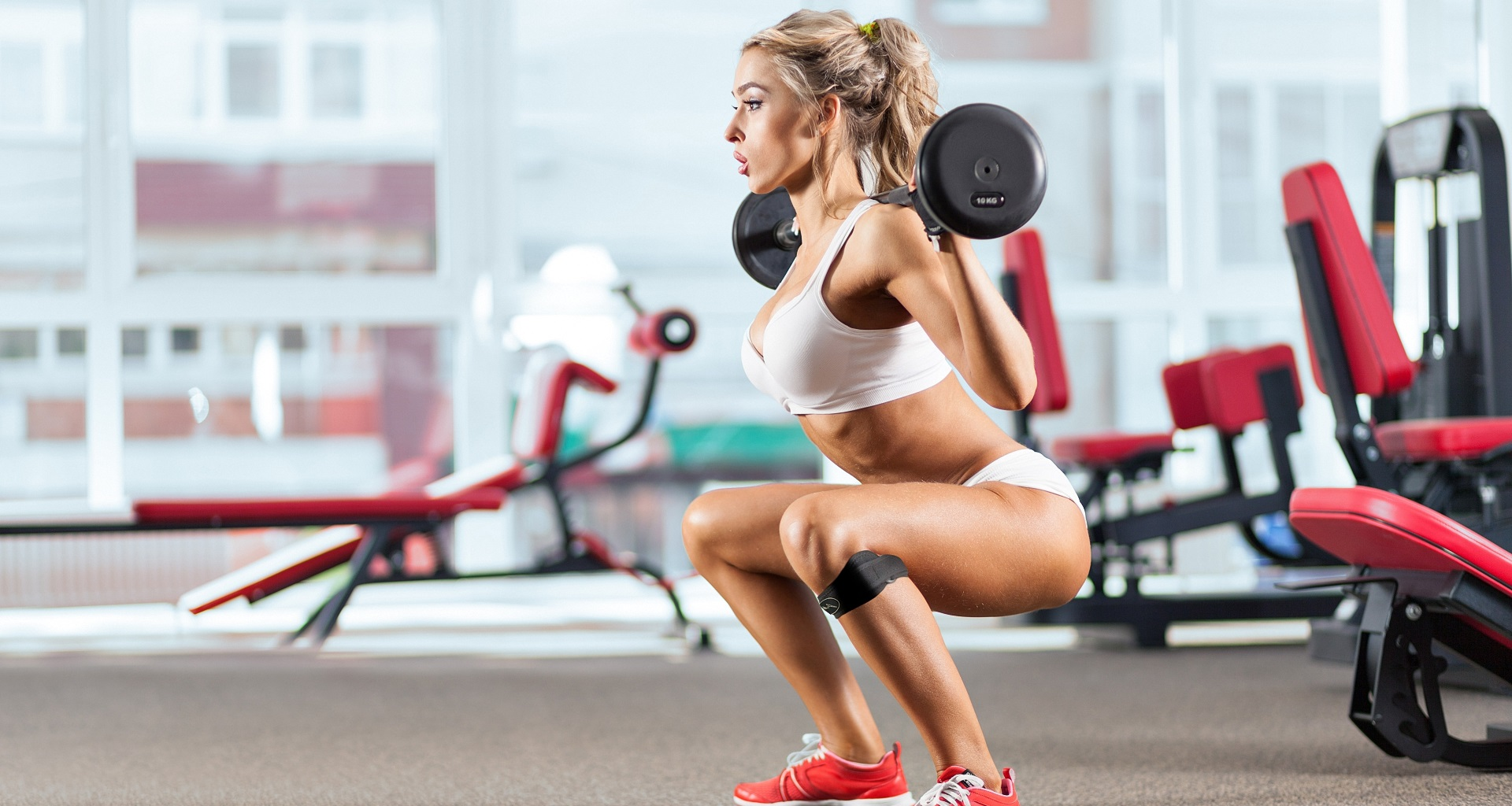 fit girl with barbell doing squatts