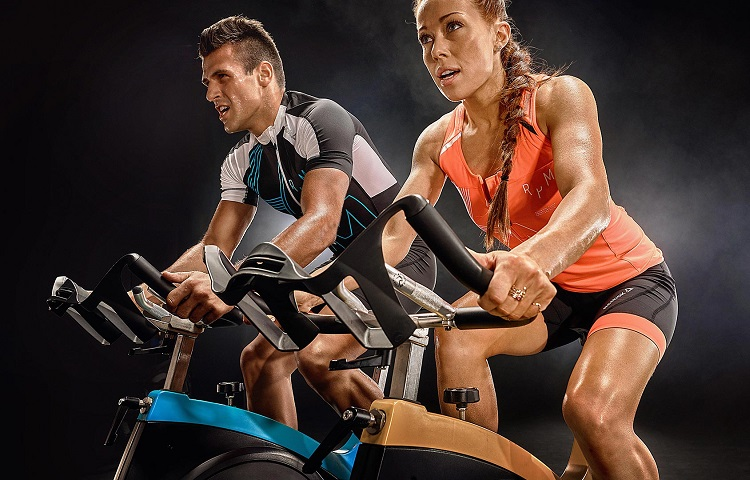 young couple training on spinning bike
