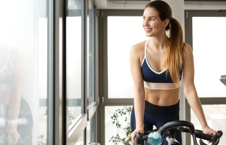 Woman riding on stationary bicycle